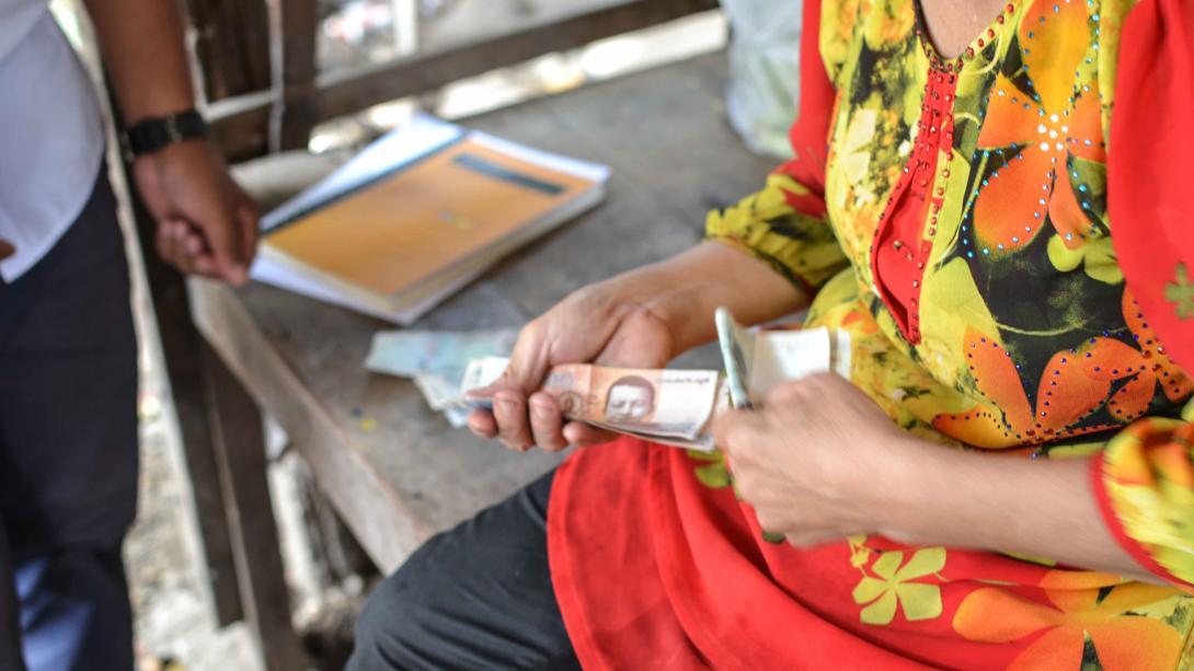 Beneficiaria de nuestro Proyecto de Microfinanzas pagando su crédito.